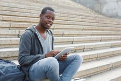 Smiling student sitting on stairs using tablet. Smiling african-american student sitting on stairs working with digital tablet, preparing for exams outdoors Royalty Free Stock Image