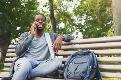 Smiling african-american student talking on the phone outdoors. Smiling african-american student sitting and talking on the phone on the bench outdoors, in Stock Photography