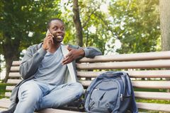 Smiling african-american student talking on the phone outdoors. Happy smiling african-american student sitting and talking on the phone on the bench outdoors in Stock Photo
