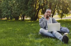 Smiling african-american student talking on phone and using laptop outdoors Stock Image