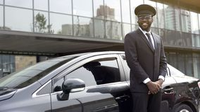 Smiling African-American taxi service driver expecting client near luxury car. Stock photo Royalty Free Stock Photos
