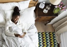 Smiling African American woman on bed using a cellphone Stock Images