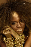 Smiling African or American woman with black curly hair, gold makeup and accessories posing holding hands near face Stock Images