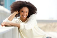 Smiling african american woman with curly hair sitting outdoors Stock Image