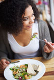 Smiling african american woman eating in restaurant Stock Photos
