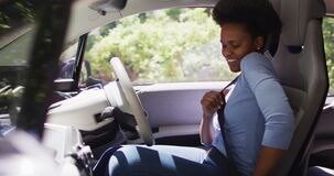 Smiling african american woman sitting in car putting on seatbelt