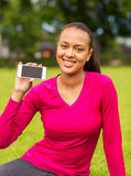 Smiling african american woman with smartphone. Fitness, park, technology and sport concept - smiling african american woman showing smartphone outdoors Stock Images