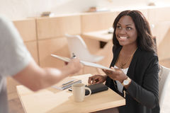 Smiling african american woman taking a bill in cafe royalty free stock image