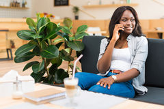 African american woman talking on smartphone while sitting in cafe royalty free stock photos