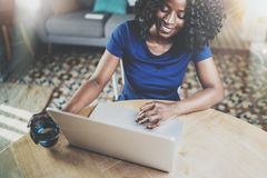 Smiling african american woman using laptop while sitting at wooden table in the living room.Horizontal.Blurred Stock Photo