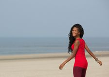 Smiling african american woman walking at the beach Stock Photography