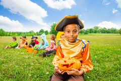 Smiling African boy in pirate costume and pumpkin Stock Images