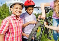 Smiling African boys in helmets repair bike royalty free stock photo