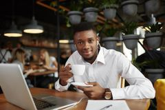 Smiling african man at coffee break in cafe. Smiling african business man sitting at restaurant with loft interior working, drinking coffee, looking at camera Stock Photography