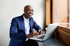 Smiling african businessman at a cafe with his laptop Royalty Free Stock Photos