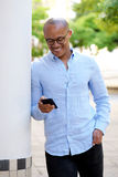 Smiling african businessman with cellphone Stock Photography