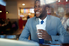 Smiling African Businessman in Coffee Shop Royalty Free Stock Photo