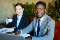Smiling African Businessman at Meeting with Colleague stock image