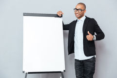 Smiling african businessman standing near flipchart and showing thumbs up Royalty Free Stock Images