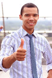 Smiling african businessman with thumbs up. Outdoors Stock Photography
