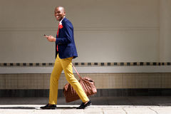 Smiling african businessman walking with bag and phone. Full length portrait of smiling young african businessman walking outdoors with bag and phone Stock Photos