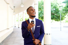 Smiling african businessman walking with cell phone in the city Royalty Free Stock Photo