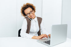 Smiling african businesswoman using laptop and talking on cell phone Royalty Free Stock Images
