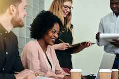 Smiling African businesswoman working with colleagues in an offi stock image