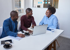 Smiling African colleagues using a laptop together in an office Stock Image
