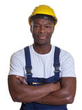 Smiling african construction worker with crossed arms stock photography