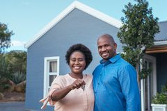 Smiling African couple standing with keys to their new home. Portrait of a smiling African couple standing arm in arm together outside holding the keys to their royalty free stock photos