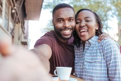 Smiling African couple taking selfies together at a sidewalk cafe. Smiling young African couple sitting at a sidewalk cafe table taking selfies while out on a royalty free stock photo