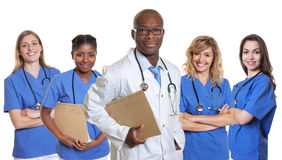 Smiling african doctor with 4 nurses royalty free stock photos