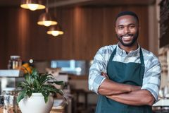 Smiling African entrepreneur standing at the counter of his cafe Stock Image