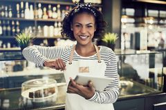 Smiling African entrepreneur standing in her cafe with a tablet royalty free stock images