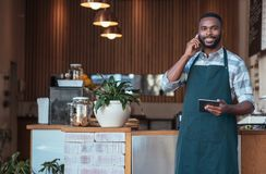Smiling African entrepreneur talking on a cellphone in his cafe. Portrait of a young African entrepreneur standing in front of the counter of his cafe talking on royalty free stock image