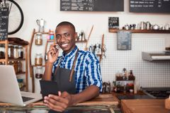 Smiling African entrepreneur talking on the phone in his cafe. Smiling young African entrepreneur standing at the counter of his cafe reading from a notebook and Stock Photography