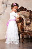Smiling african  girl with curly hair in a white lace dress on vintage chair Stock Photos