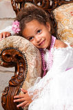 Smiling african  girl with curly hair in a white lace dress on vintage chair Stock Photography