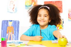 Smiling African girl holds pencil and apple Stock Photo