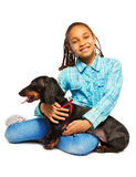 Smiling African girl hugging black dachshund Royalty Free Stock Images
