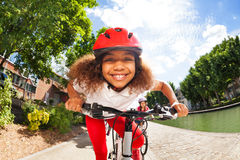 Smiling African girl riding her bicycle in summer stock photography