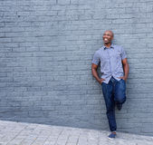 Smiling african guy leaning against gray wall Royalty Free Stock Photography