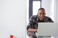 Smiling african guy working on laptop at home Royalty Free Stock Images