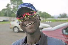 Smiling African man, a gas station attendant, wears 2 sets of colored sun glasses, South Africa Royalty Free Stock Image
