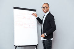 Smiling african man in glasses writing business plan on flipchart Stock Photos