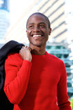Smiling african man holding coat over shoulder in the city Stock Photos