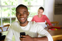 Smiling african man at home with woman using laptop in background Royalty Free Stock Photography