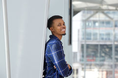 Smiling african man leaning against wall with arms crossed Stock Photo