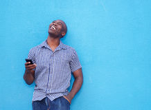 Smiling african man with mobile phone. Portrait of smiling african man with a mobile phone standing against blue background Stock Photography
